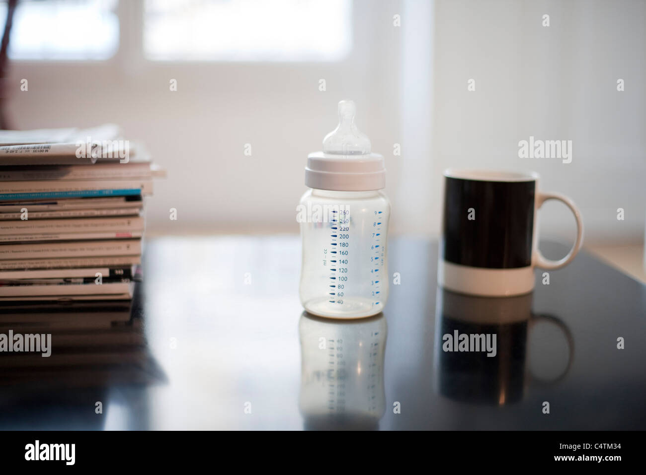 Baby bottle, coffee mug and stack of magazines - Stock Image