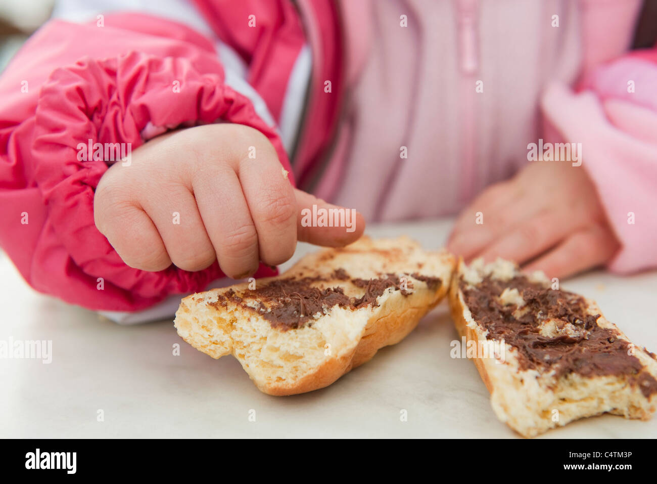 Toddler girl eating baguette with chocolate spread, cropped - Stock Image