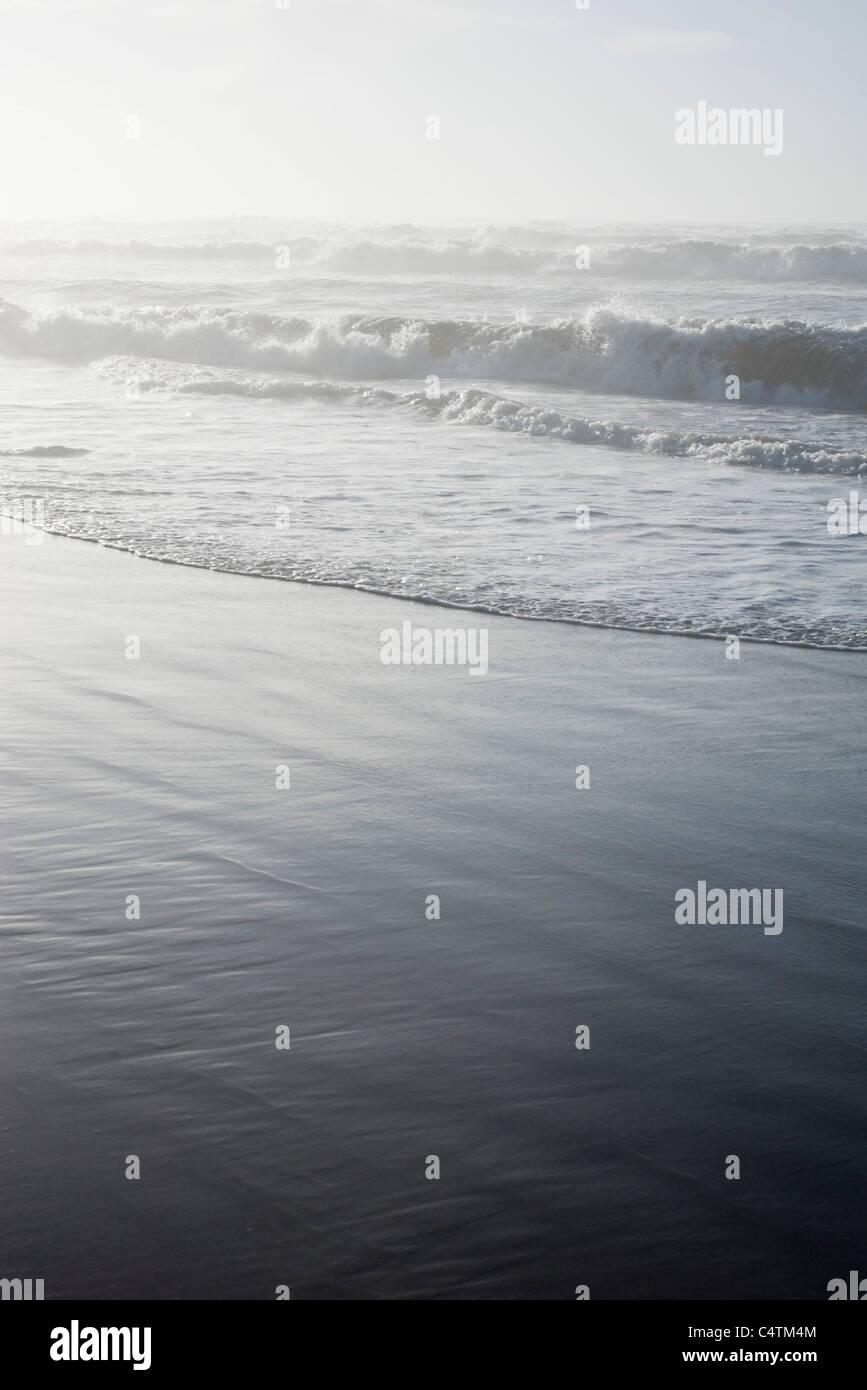Waves washing onto shore - Stock Image