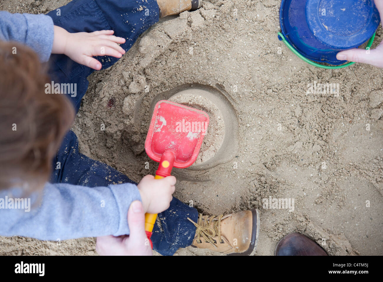 Toddler boy playing in sand - Stock Image