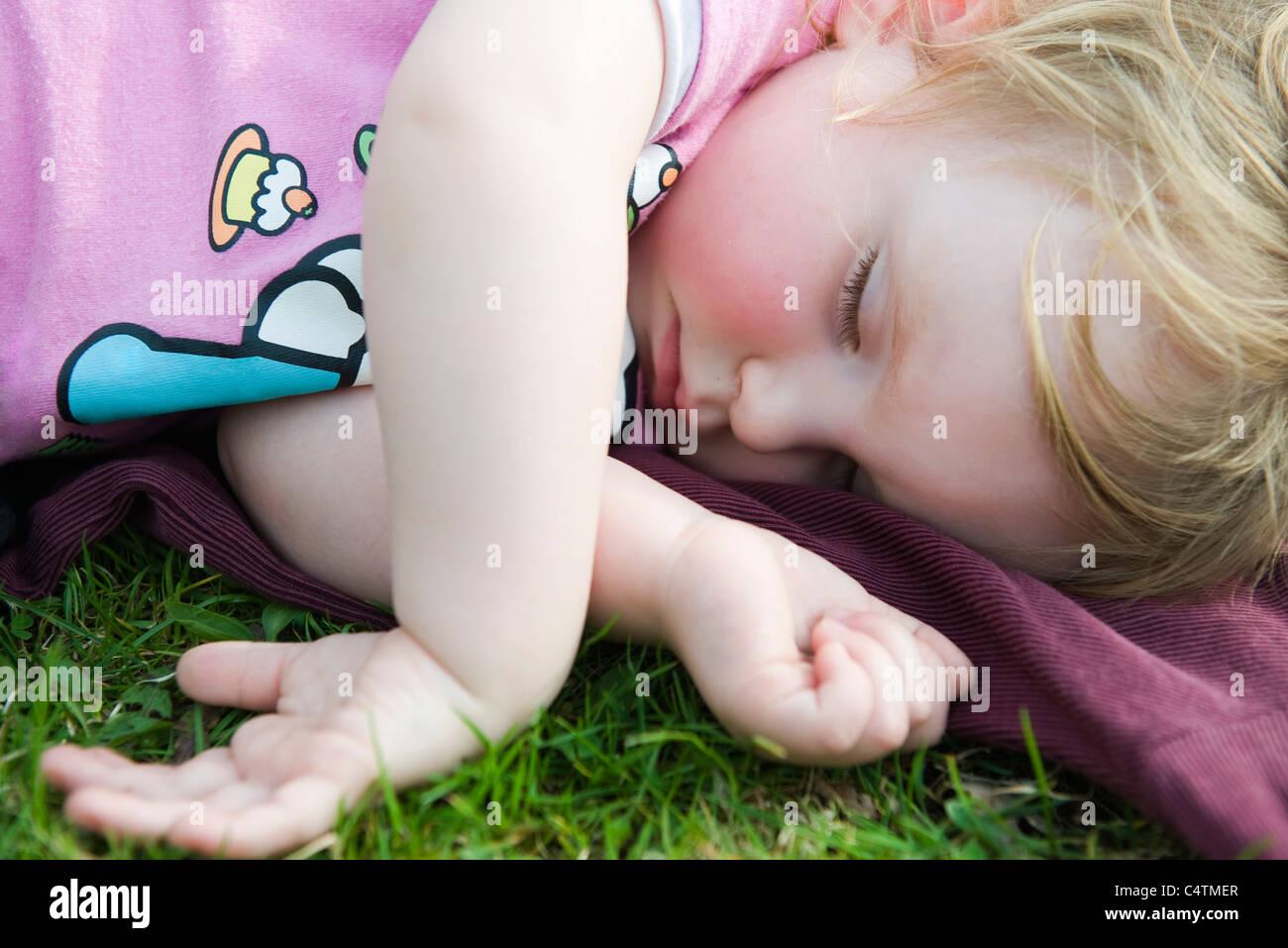 Toddler girl taking a nap outdoors Stock Photo