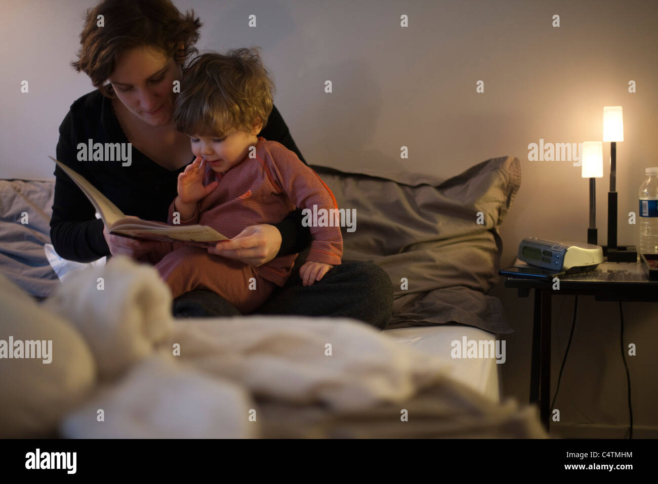 Mother holding toddler son on lap, reading bedtime story in bed - Stock Image