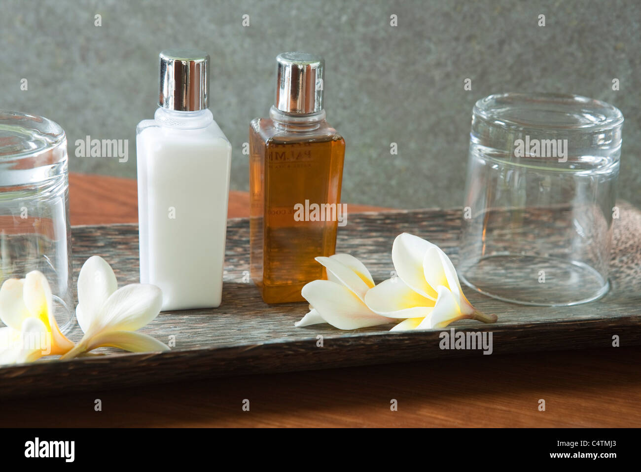 Perfume bottle and glasses on tray with frangipani flowers - Stock Image