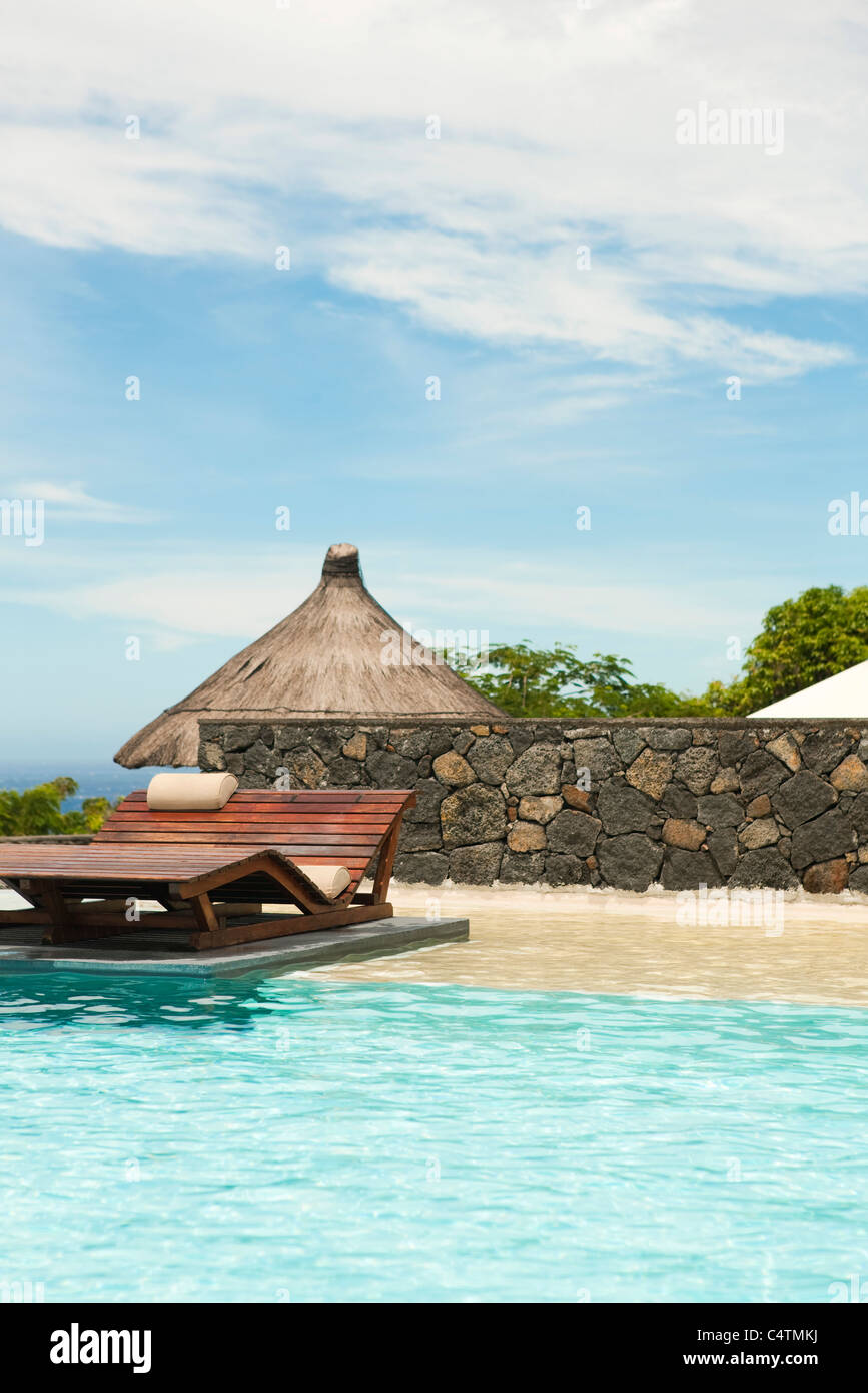 Wooden lounge chair in pool at resort - Stock Image