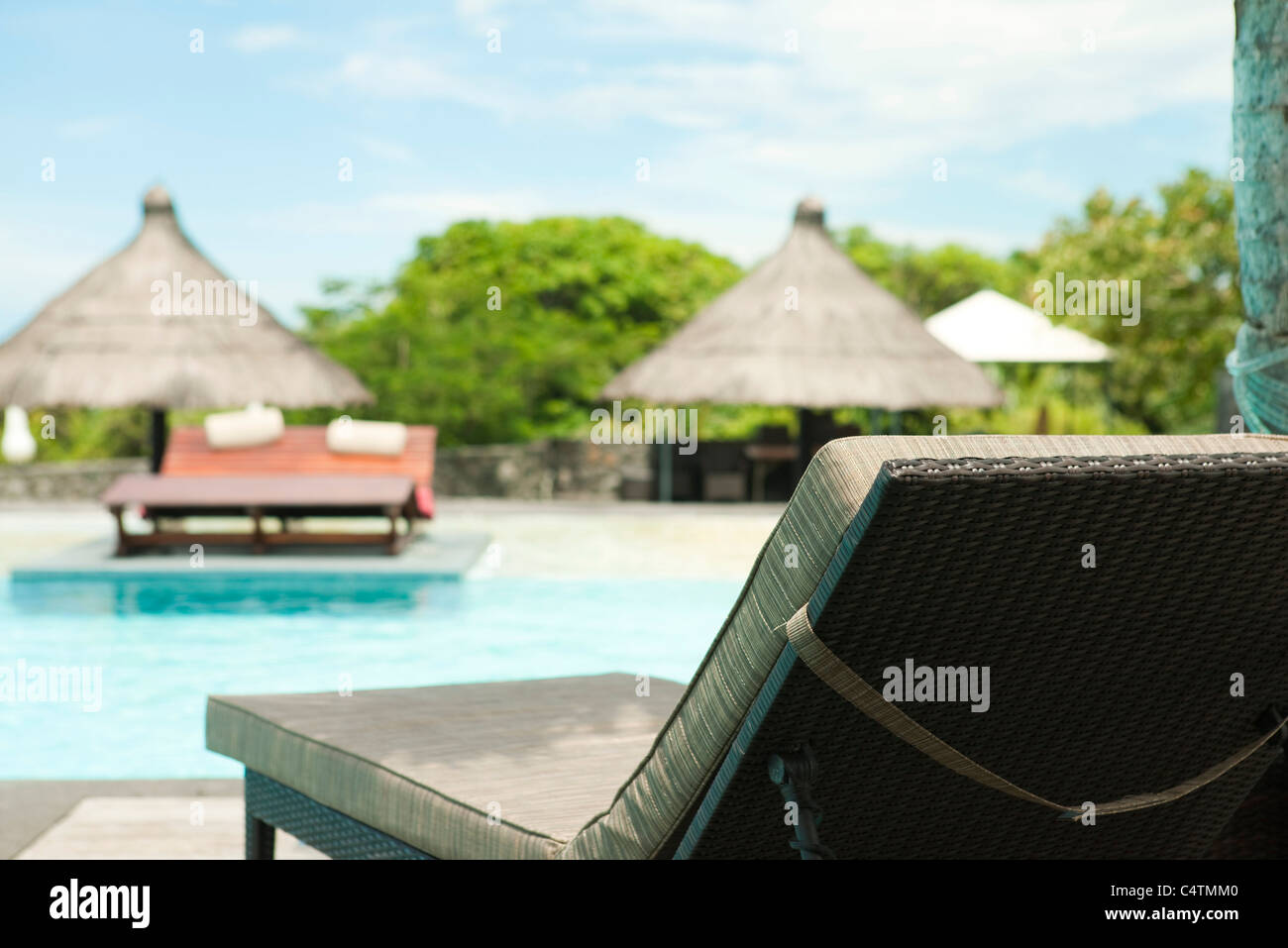 Lounge chair beside pool at resort - Stock Image