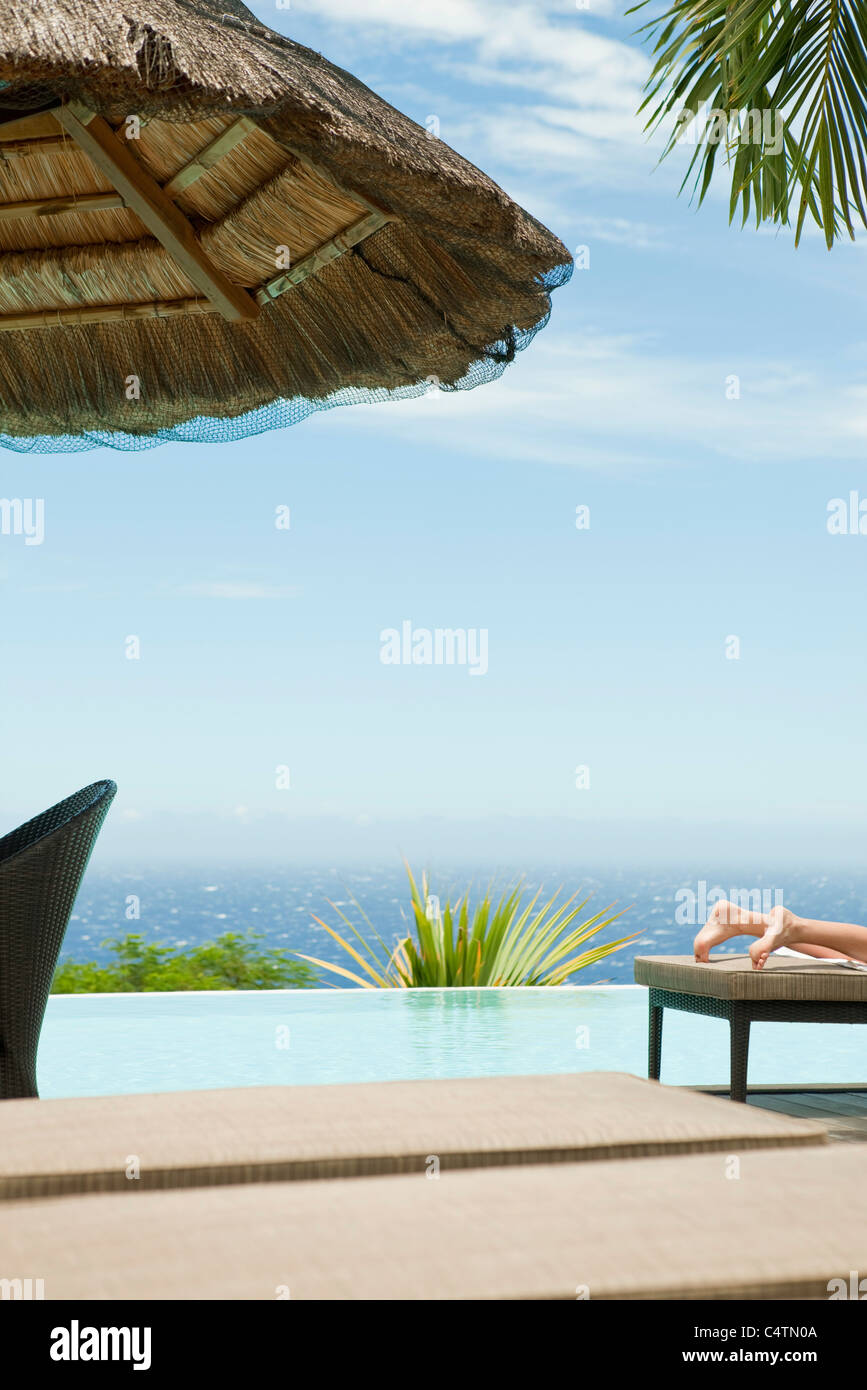 Person sunbathing at seaside resort Stock Photo