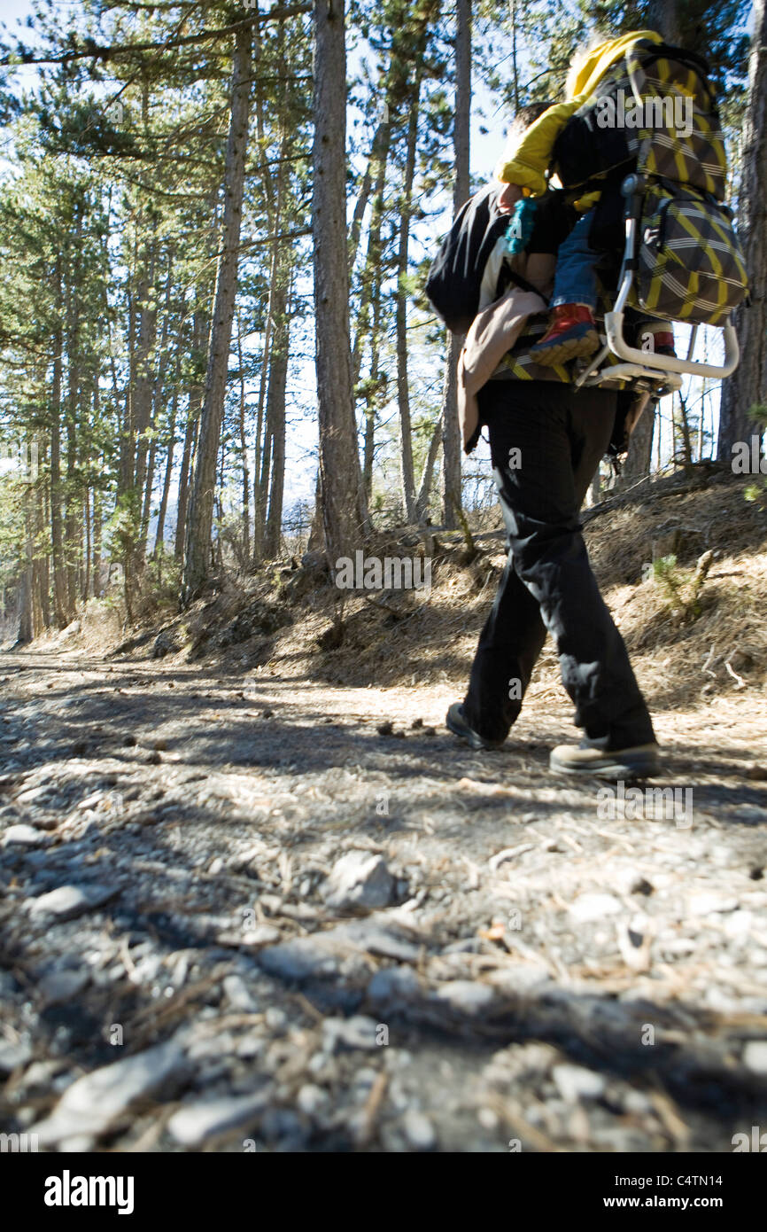 Hiker walking in woods with baby in backpack carrier, low angle view - Stock Image