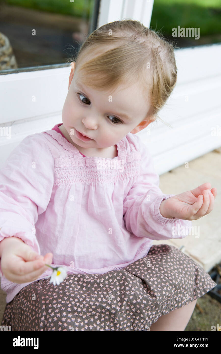 Toddler girl holding flower, looking down curiously, portrait - Stock Image