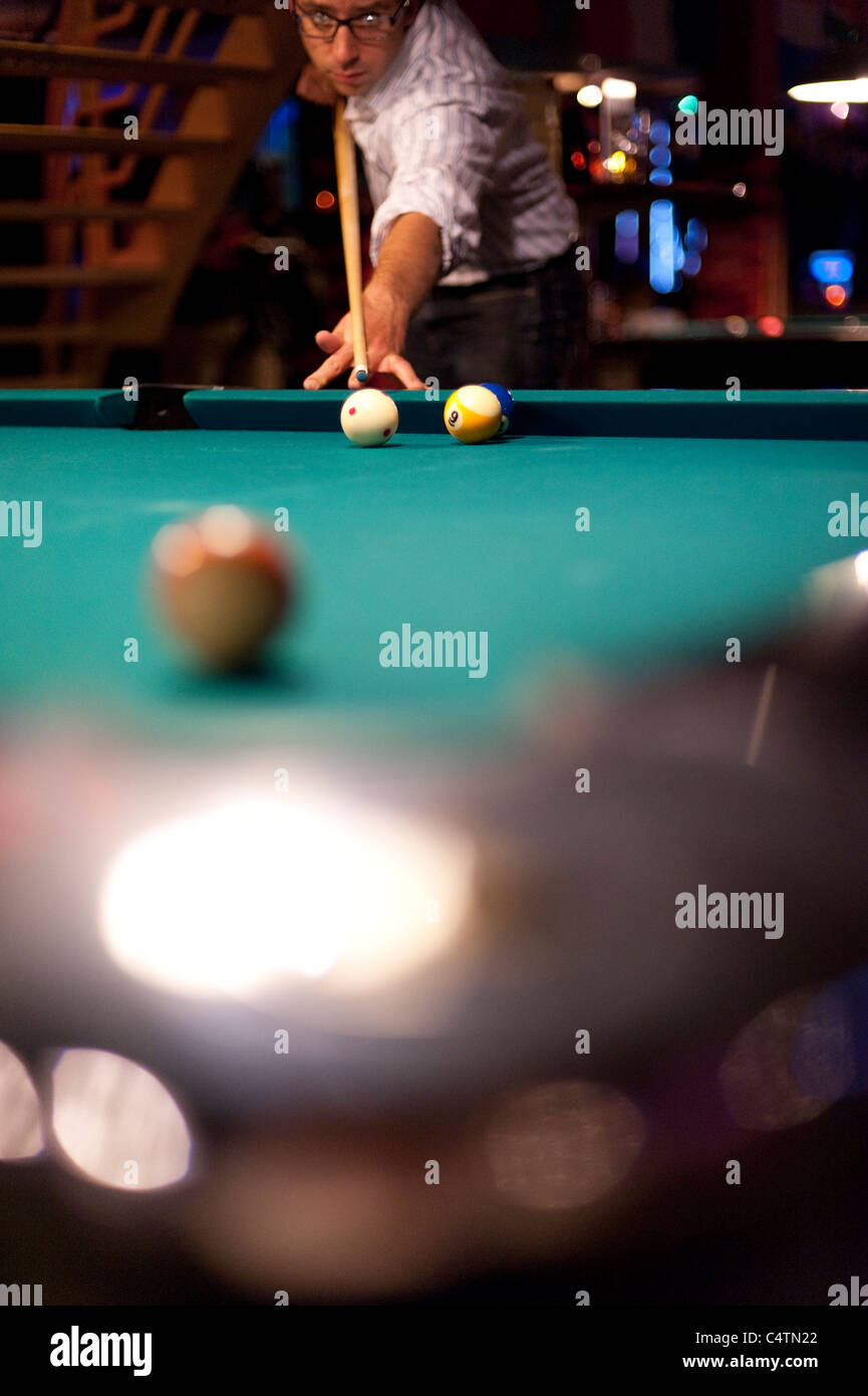 Young man playing eight ball billiards in a bar - Stock Image