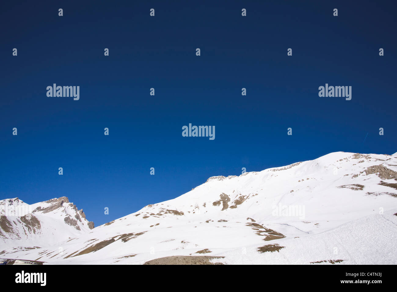 Snow-covered mountain against clear blue sky - Stock Image