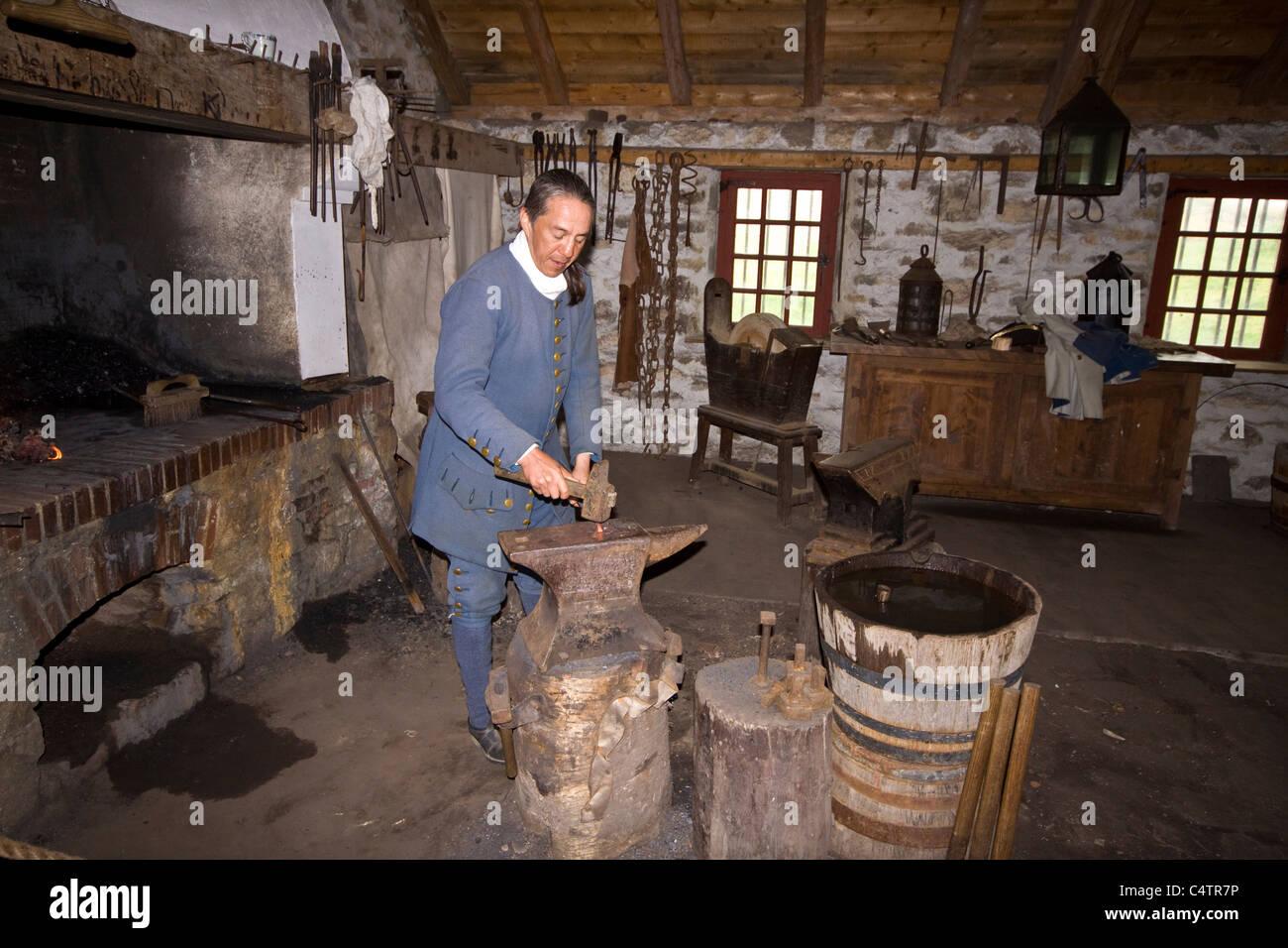 Period actor demonstrates blacksmith skills at Fortress of Louisbourg National Historic Site, Cape Breton, Nova - Stock Image