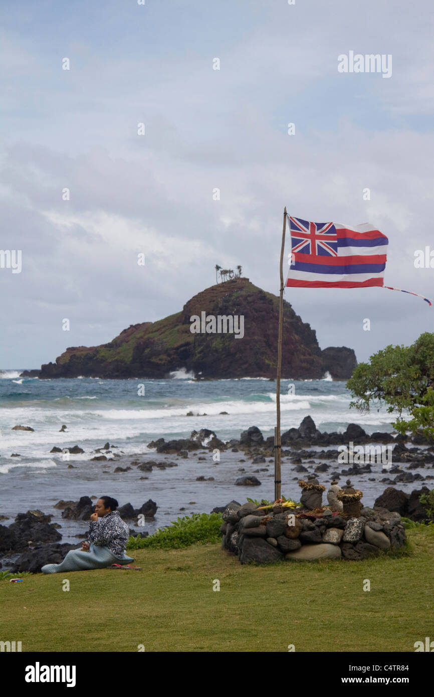 Alau Island with Hawaiian flag and sitting islander in the foreground, Hamoa, near Hana, Maui, Hawaii - Stock Image
