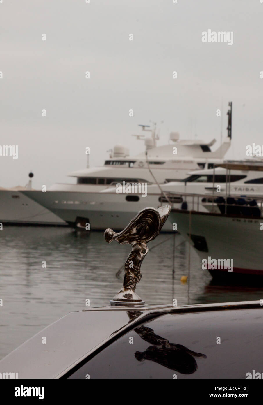 rolls royce wings in front of luxury yachts in puerto banus harbour marbella spain on a slightly overcast day