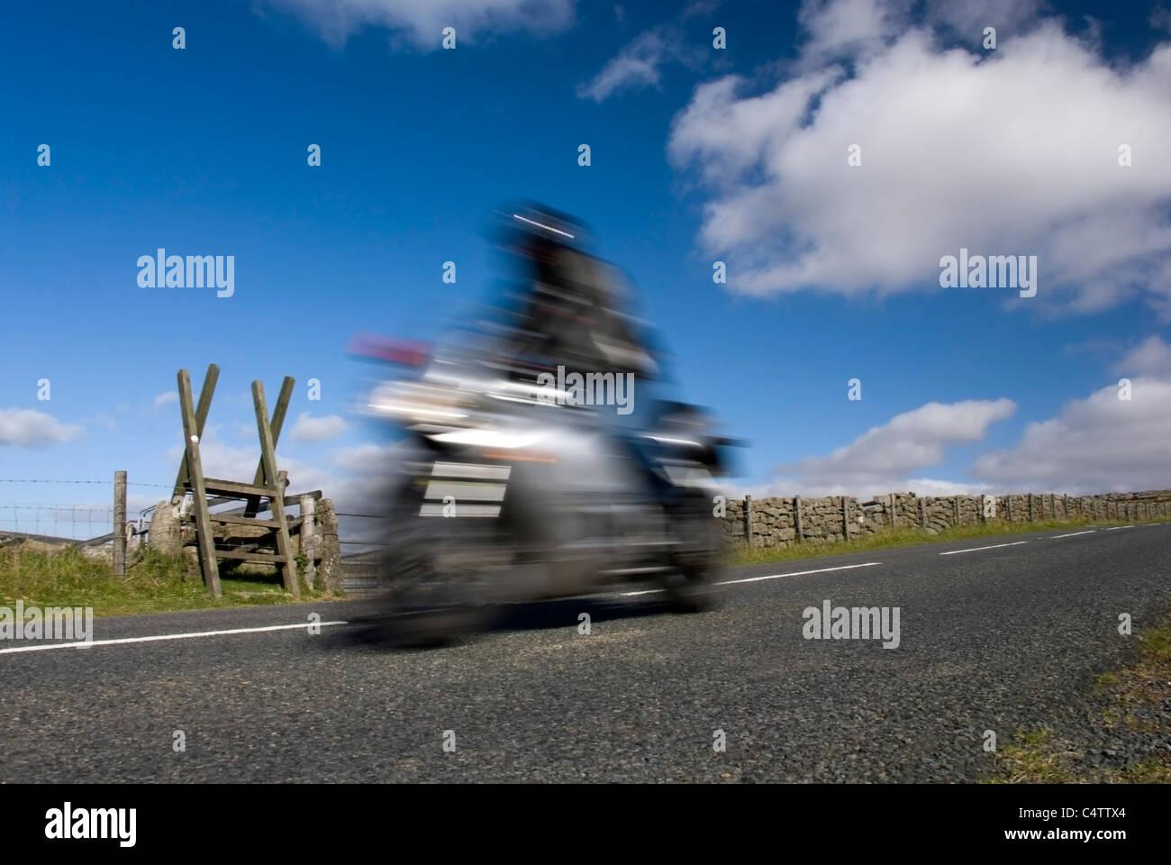 Blurred speeding motorbike on mountain road. Dartmoor, Devon, England - Stock Image