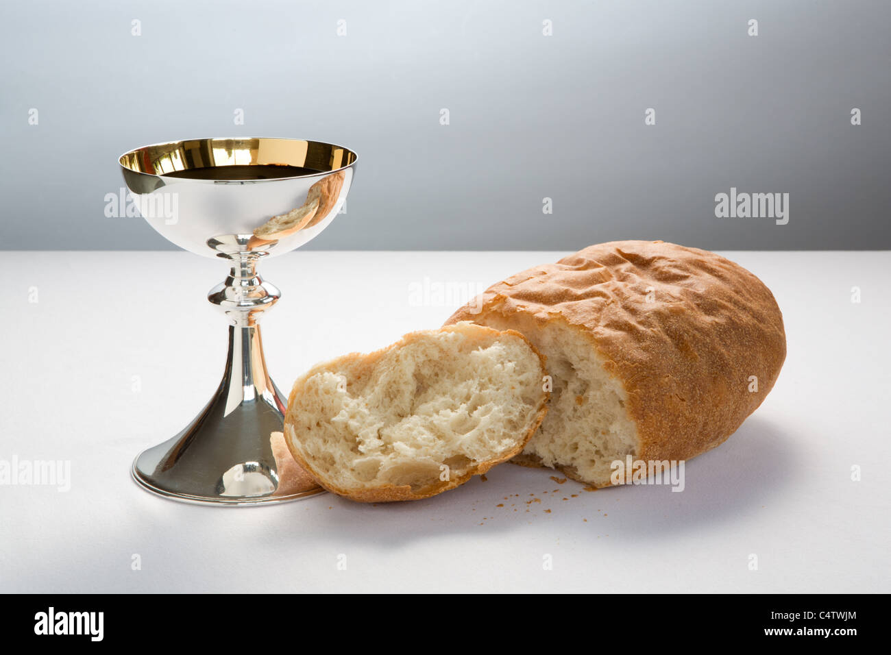 Holy Communion cup (chalice) with wine and broken loaf of