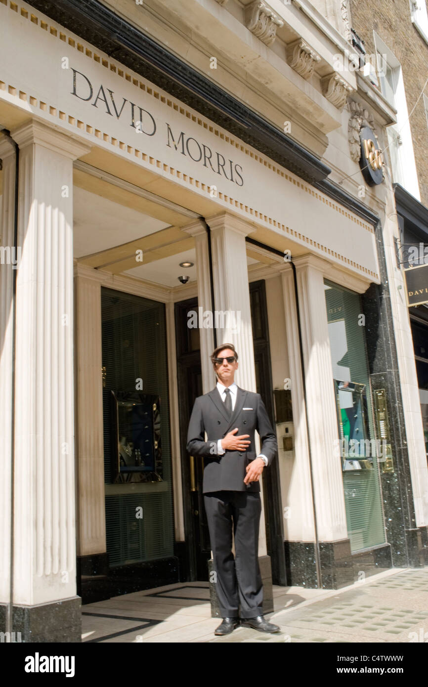London Mayfair Bond Street David Morris jewelers jewelry shop or store with dapper security guard smart double breasted - Stock Image