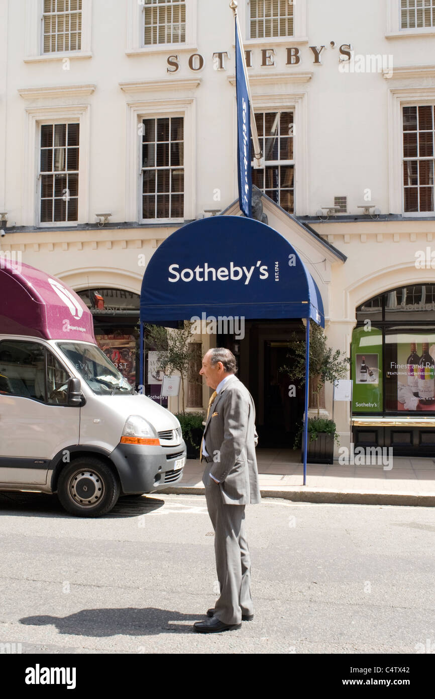 London Mayfair Bond Street smart elegant elderly man waiting in road for his chauffeur standing outside Sotherby's - Stock Image