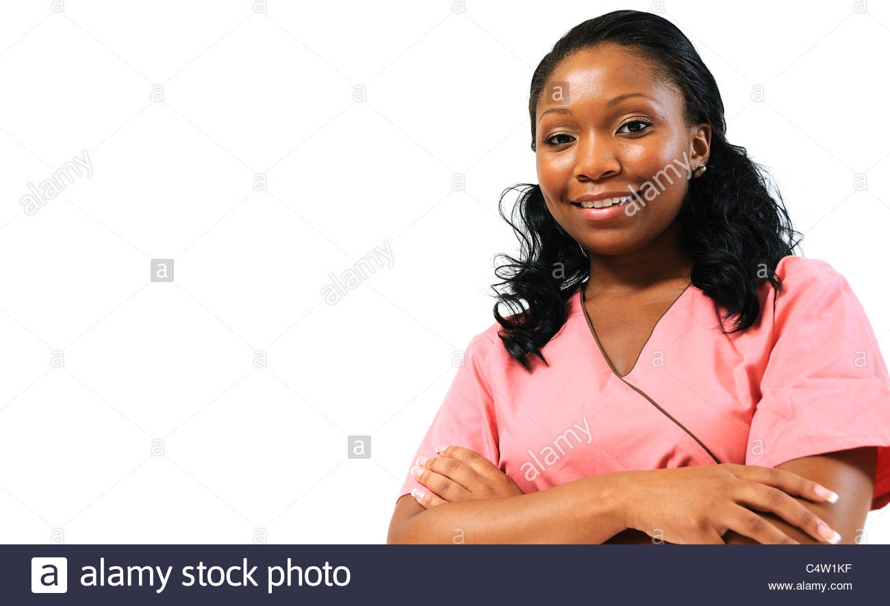 Beautiful African American female nurse or doctor with arms crossed and wearing scrubs. Smiling at viewer - Stock Image