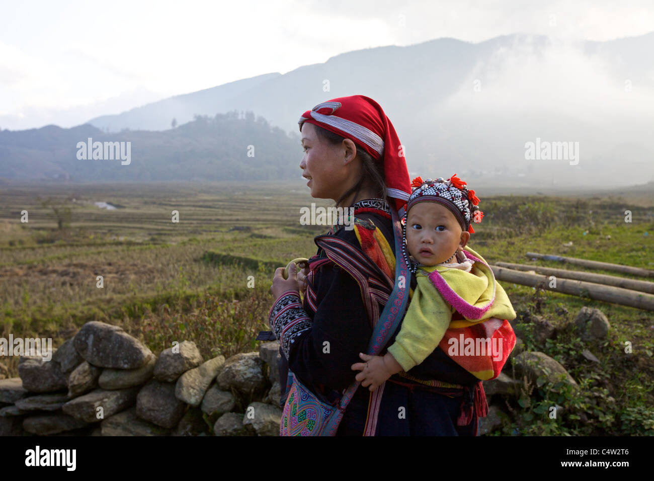 Unidentified young girl from the Red Dao Ethnic Minority people carries a baby on November 22, 2010 in Sapa, Vietnam. - Stock Image