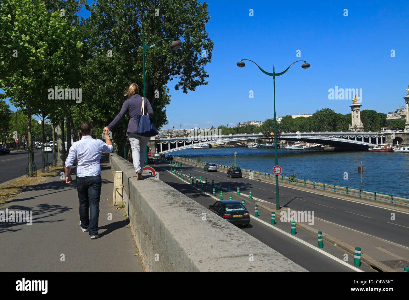 Sightseeing in Paris. A couple walk along the Quay D'Orsay beside the Seine River towards Pont Alexandre III. Stock Photo