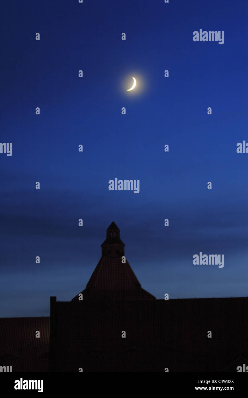 New moon over roof - Stock Image