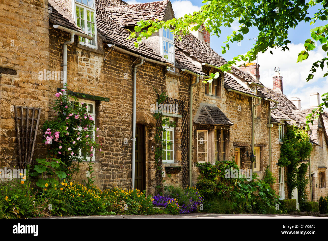 Row of pretty Cotswold stone cottages in the tourist town of Burford, Oxfordshire, England, UK - Stock Image