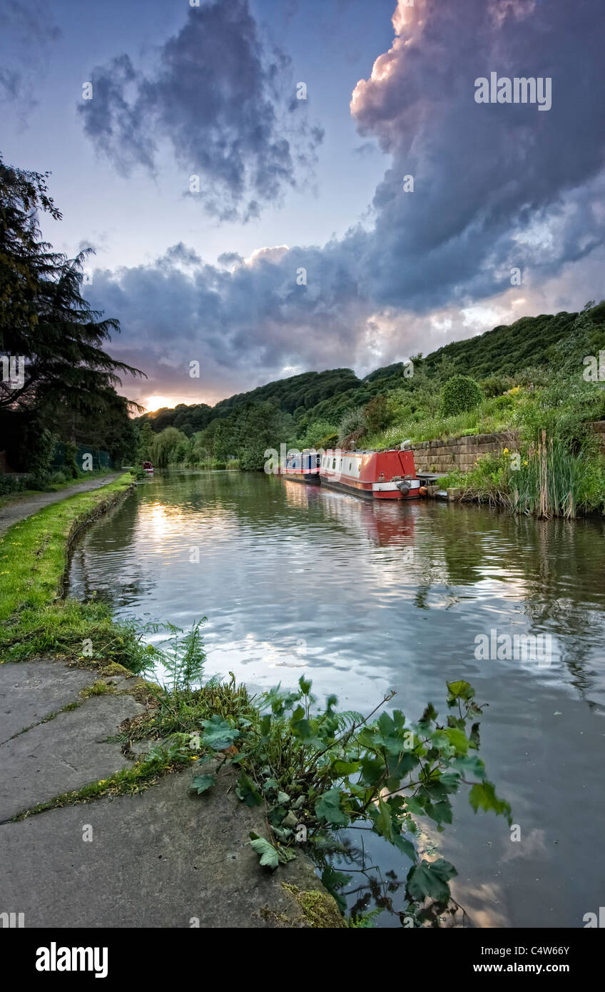 canal narrowboat on the rochdale canal sidelit by the warm glow of sunset - Stock Image