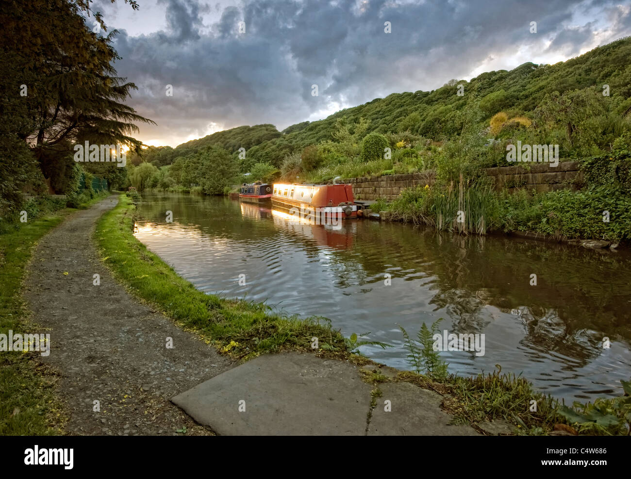 canal narrowboat on the rochdale canal sidelit by the warm glow of sunset Stock Photo
