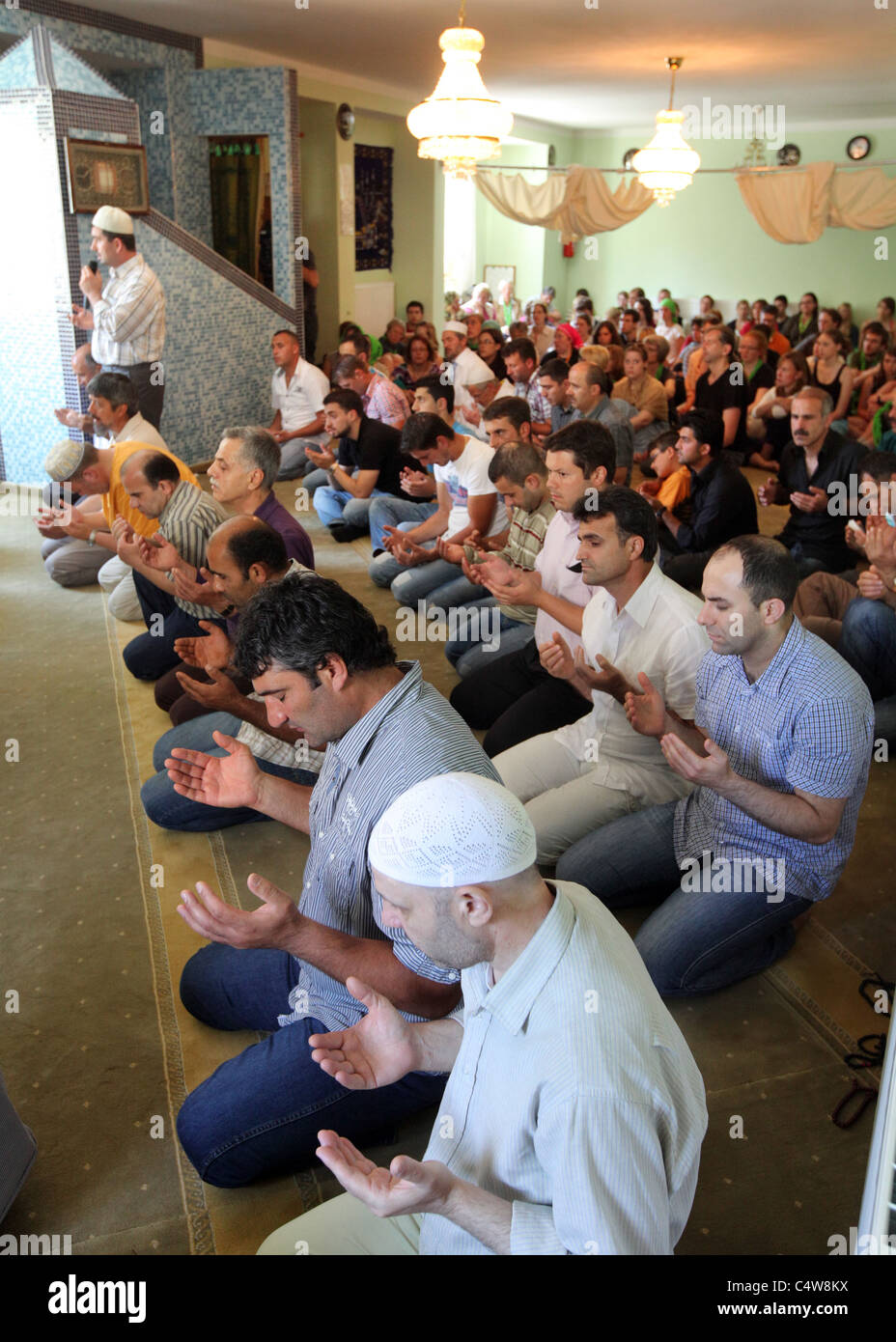turkish muslims (front) watched by german christians (back) during a friday prayer in a mosque in Dresden, Germany. - Stock Image