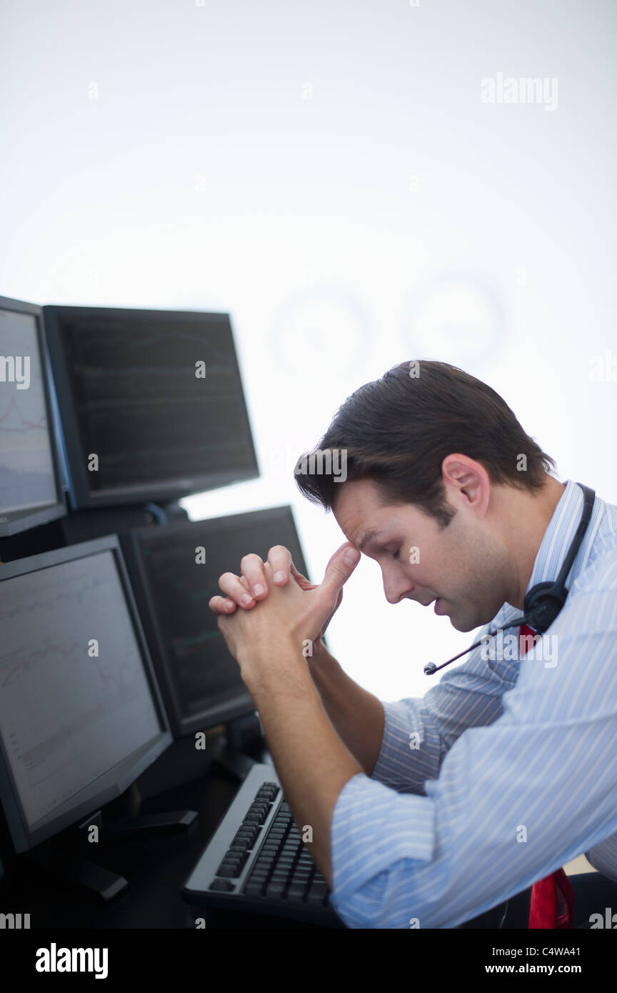 USA,New Jersey,Jersey City,upset financial worker analyzing data displayed on computer screen - Stock Image