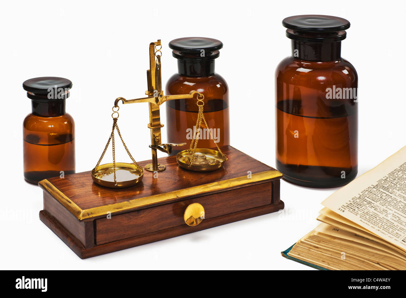 Detail photo of a old druggist balance alongside are three pharmacists bottles and a old book Stock Photo