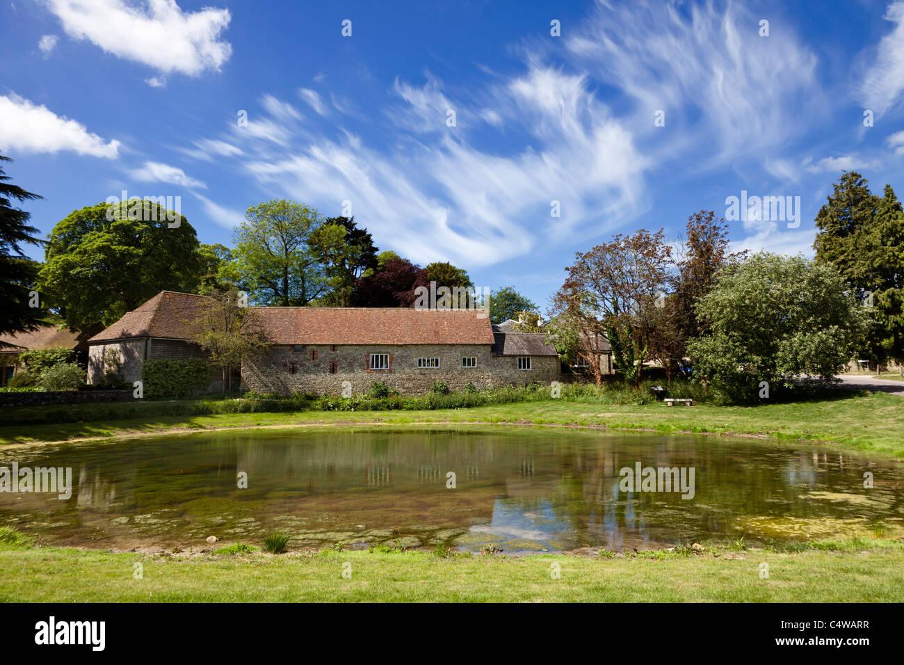 Barn conversion house and Ashmore village pond, Dorset, England, UK - Stock Image
