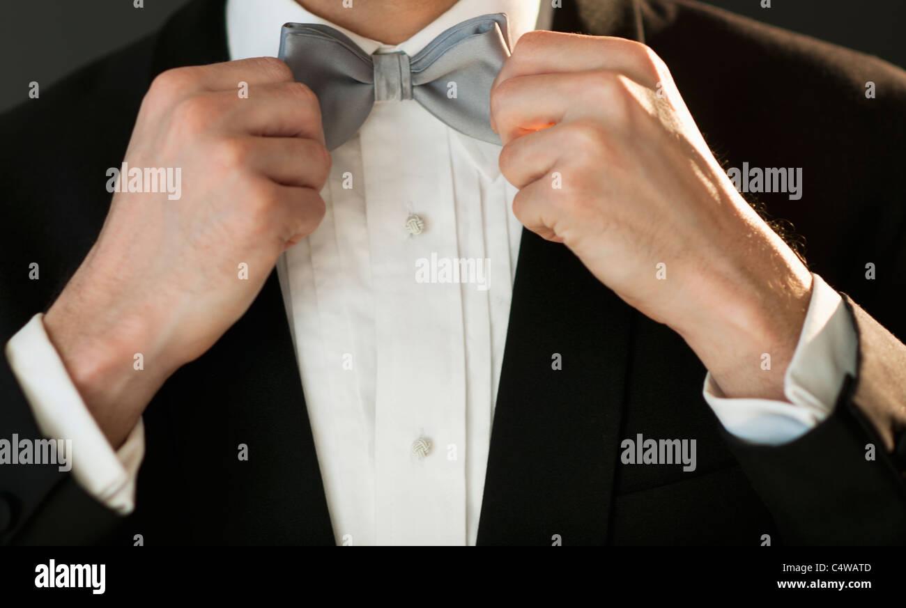 Studio shot of bridegroom adjusting bow tie - Stock Image
