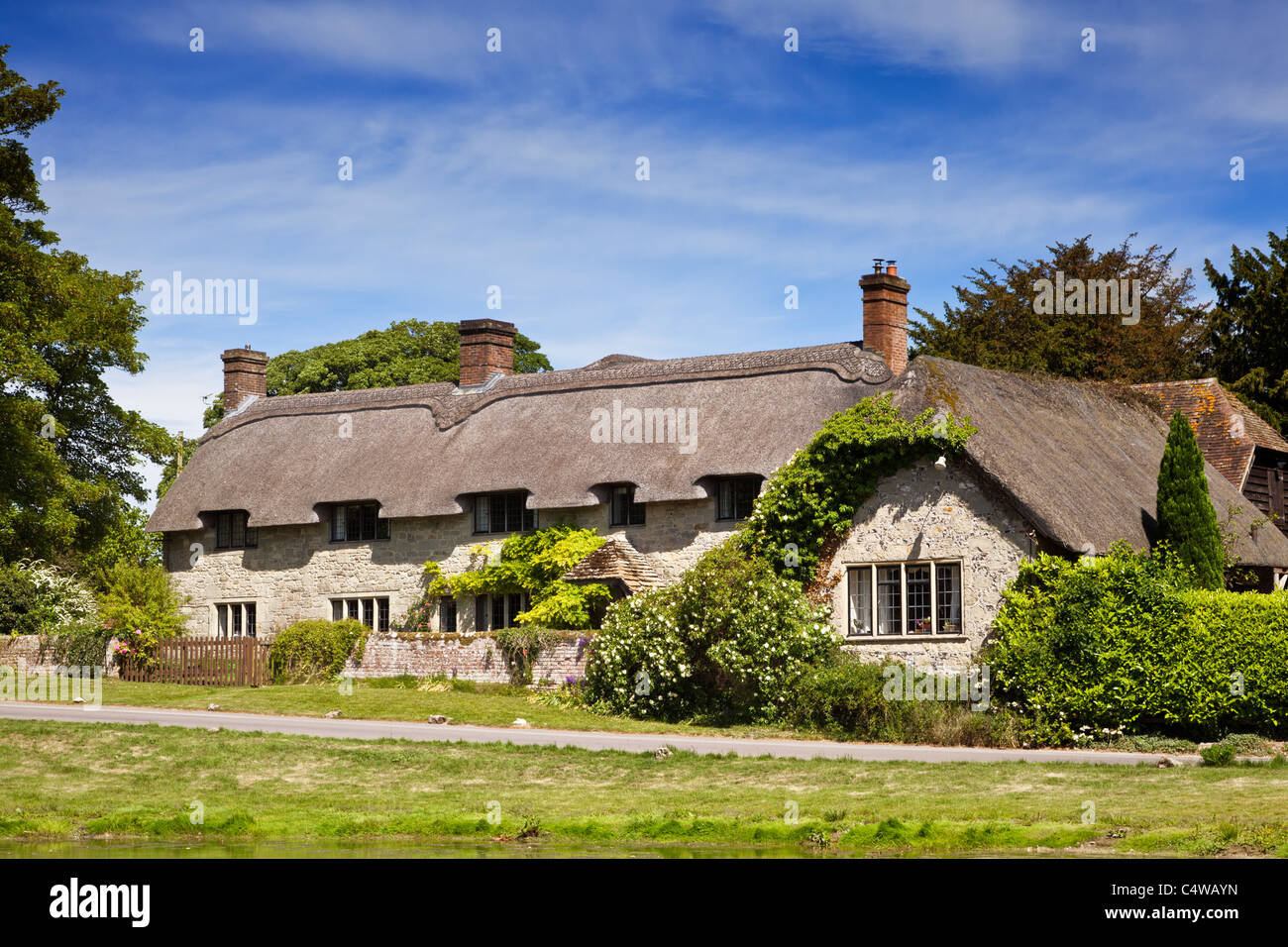 Beautiful old detached house thatched country cottage in the village of Ashmore, Dorset, England, UK in summer - Stock Image