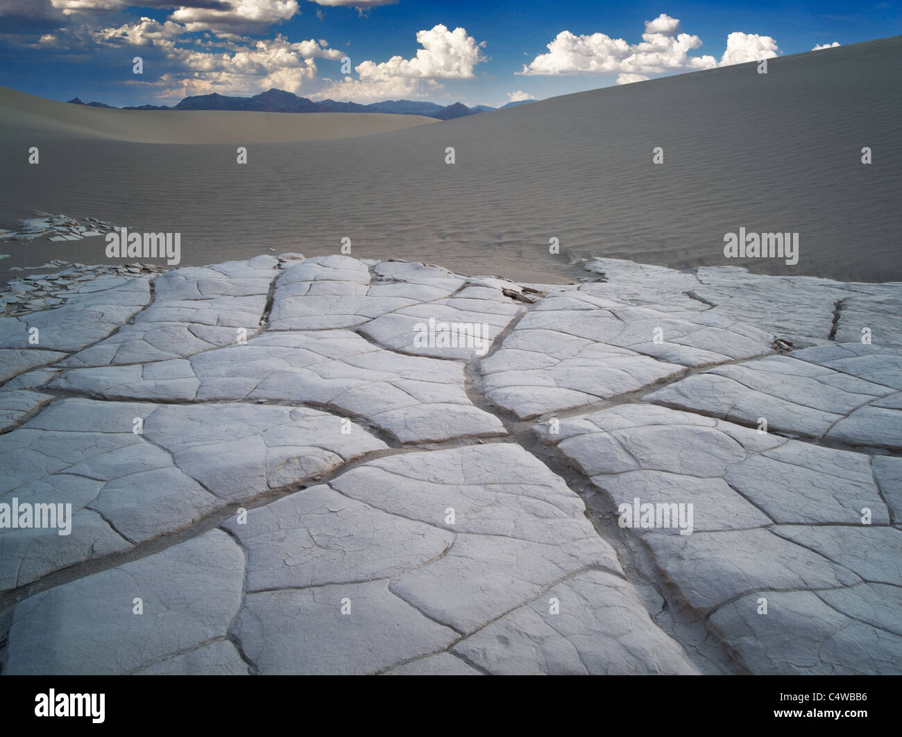 Mud patterns and dunes with sunrise. Death Valley National Park, California. Sky has been added - Stock Image