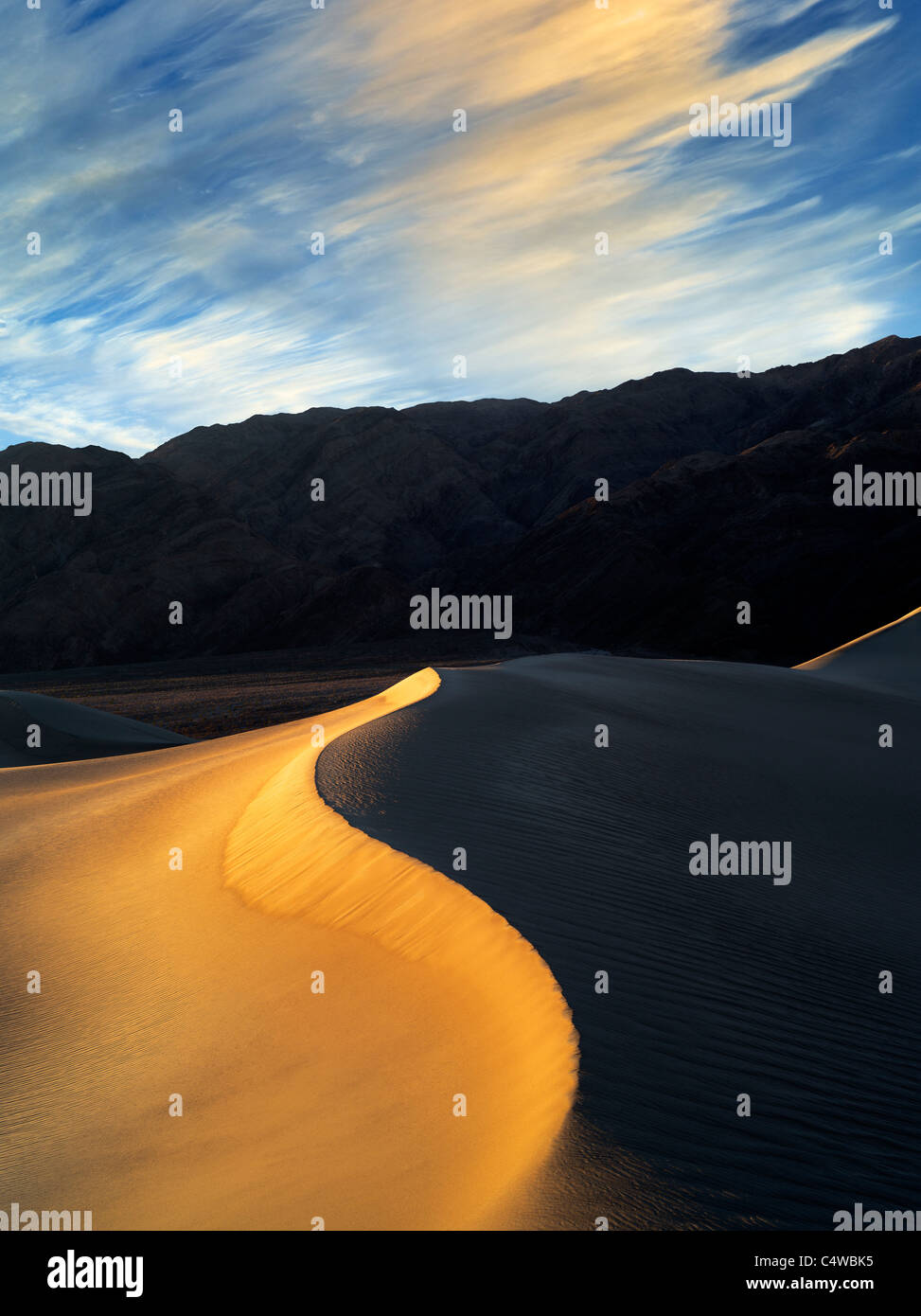 First light on sand dunes. Death Valley National Park, California. Sky has been added - Stock Image