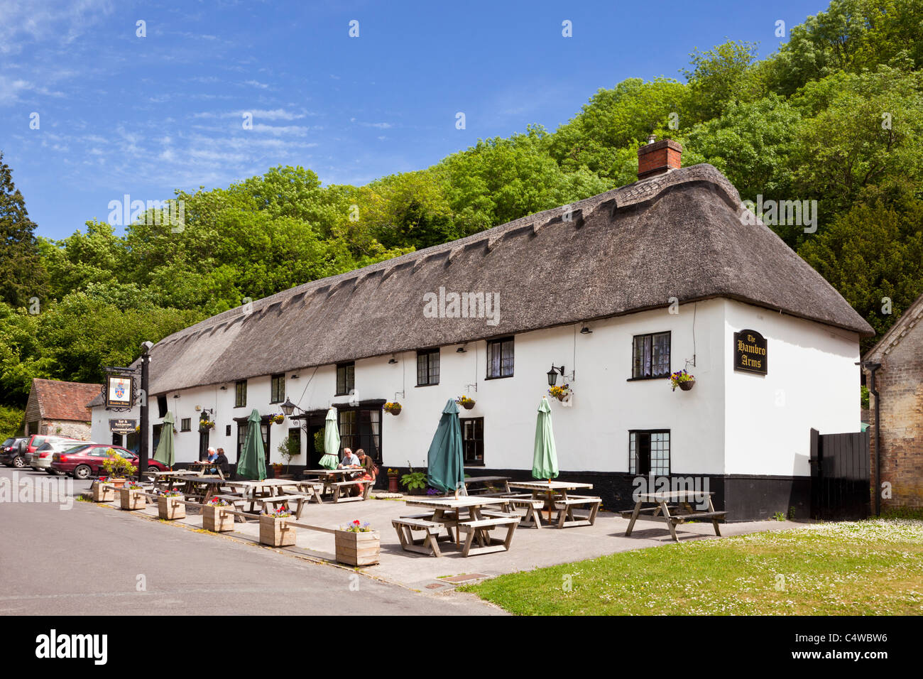 The Hambro Arms village pub with thatched roof in the pretty English village of Milton Abbas, Dorset, England, UK - Stock Image