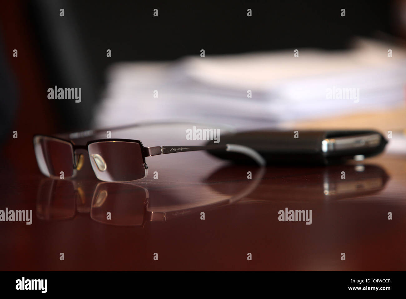 Glasses, mobile phone and paperwork on table. - Stock Image