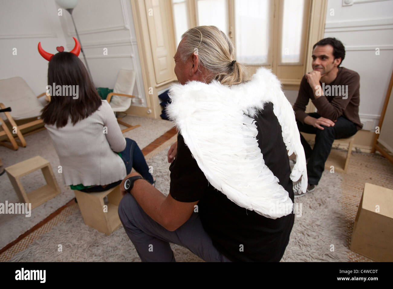 Psychodrama therapy session with man and woman playing the role of devil and angel. - Stock Image