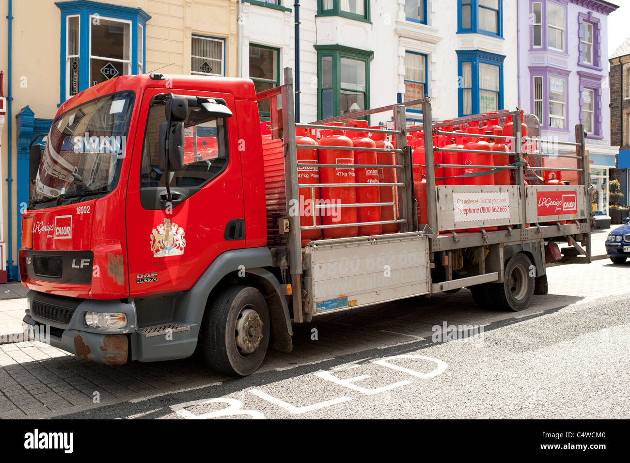 A delivery of orange coloured Calor propane gas bottles cylinders, UK - Stock Image