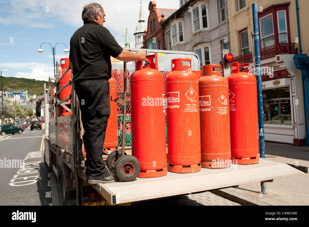 A man with a delivery of orange coloured Calor propane gas bottles cylinders, UK - Stock Image