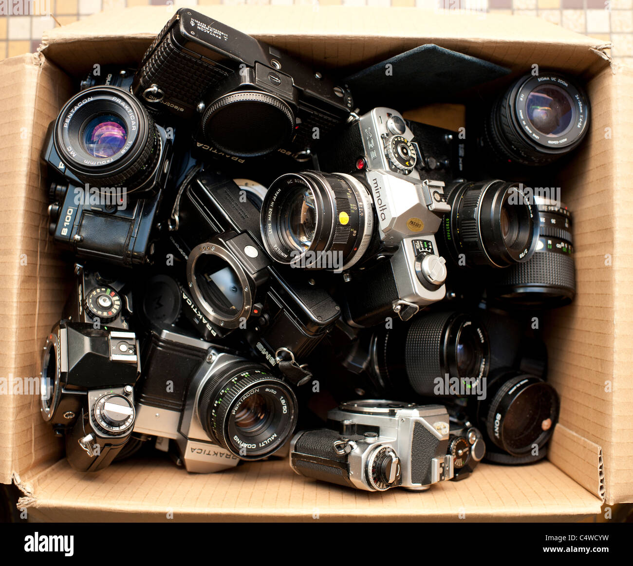 a cardboard box of assorted used old second hand 35mm old film SLR camera bodies and lenses, UK - Stock Image