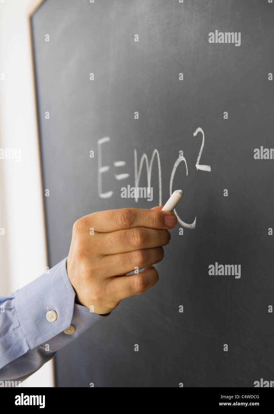 Close-up of man's hand writing theory of relativity formula on blackboard - Stock Image