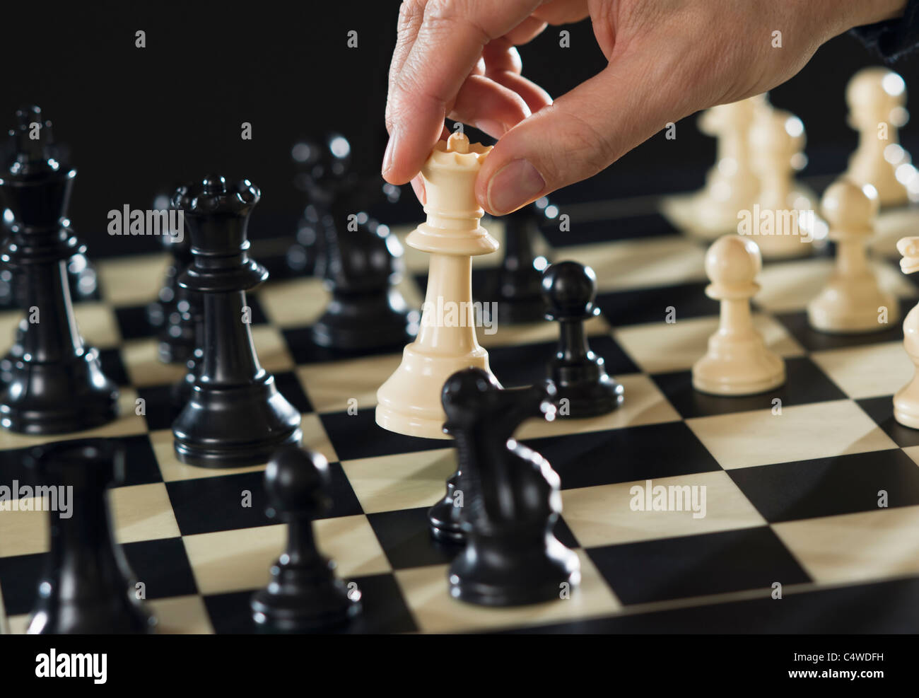 Close-up of man's hand playing chess - Stock Image