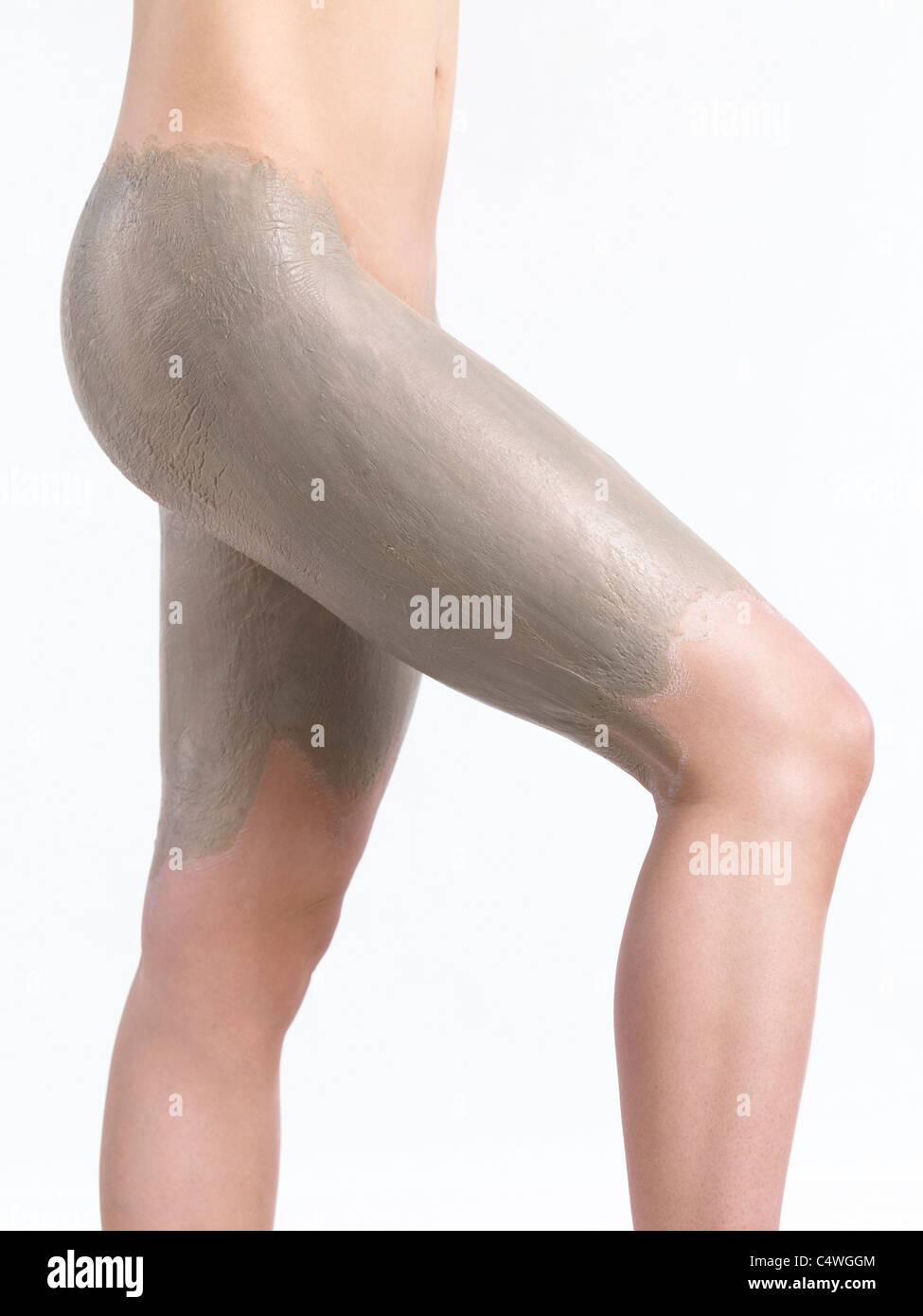 Woman with bentonite clay body wrap mask on her thighs and buttocks - Stock Image