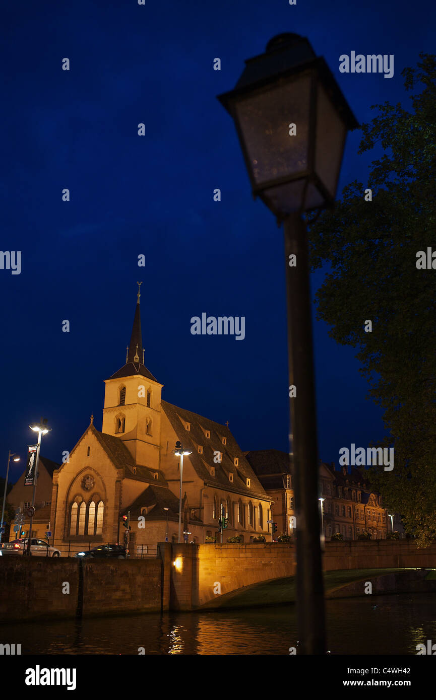 Protestant church Saint-Nicolas, Strasbourg in blue hour with lantern and bridge - Stock Image