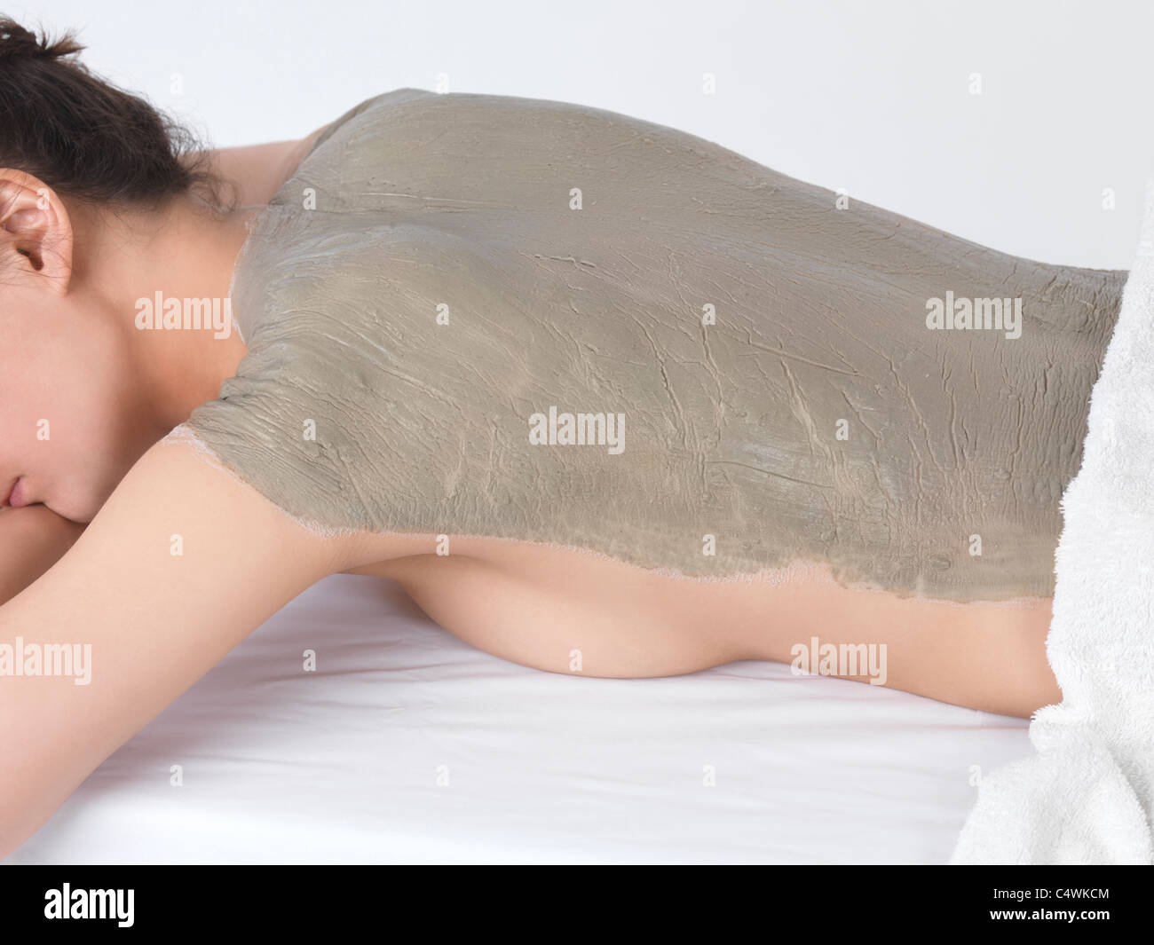 Woman with bentonite clay body wrap mask on her back - Stock Image