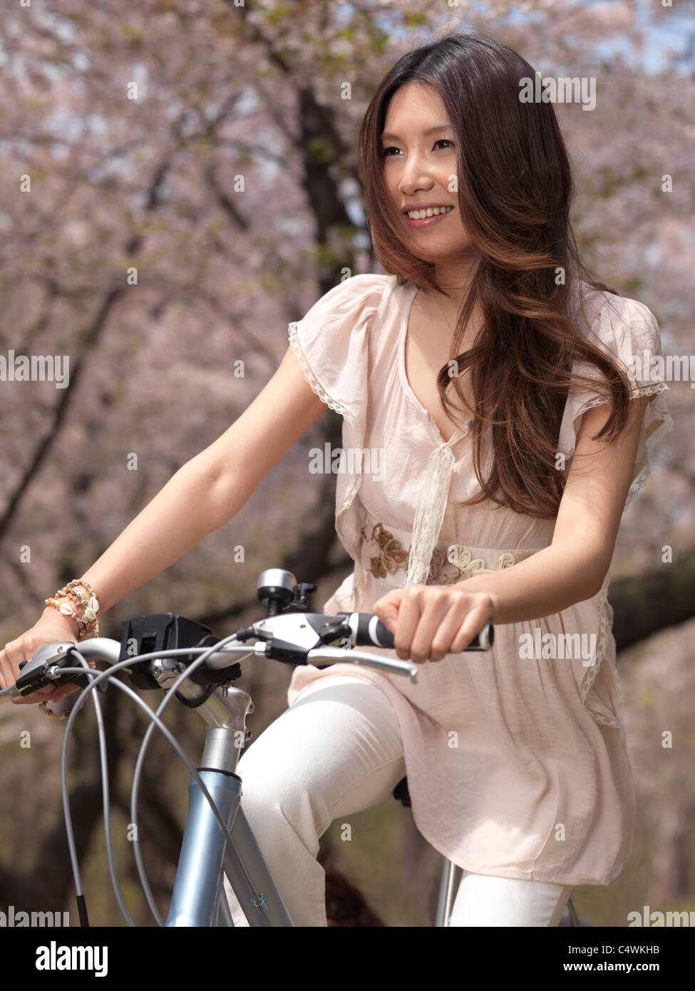 Young smiling Asian woman riding a bicycle in a park past blooming cherry trees Stock Photo