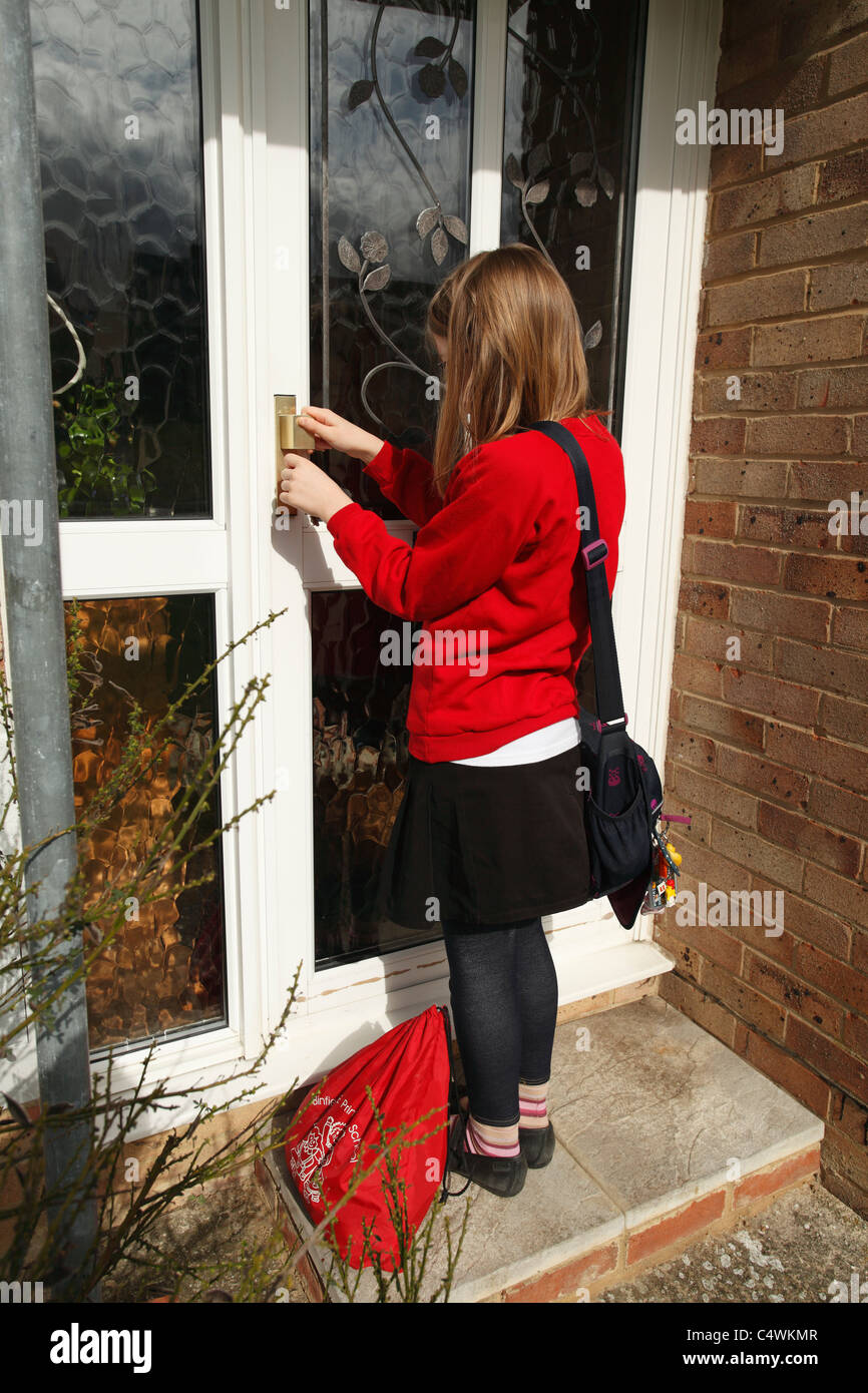Latch Key Kid, Young Girl, 9, letting herself into home after school - Stock Image