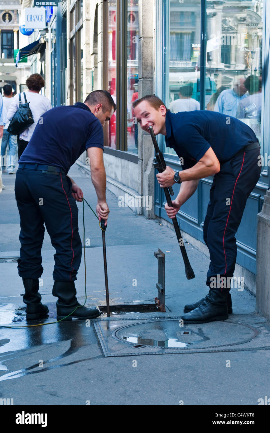 Two utilities men turning the water off / on, in the High Street - Stock Image